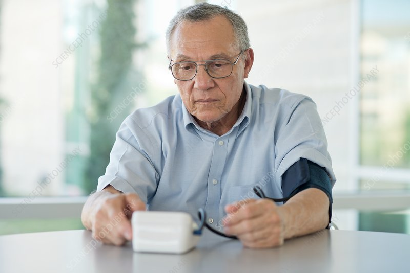 Senior man taking his own blood pressure