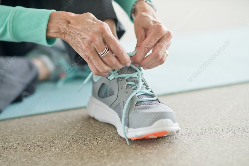 Senior woman lacing up trainers