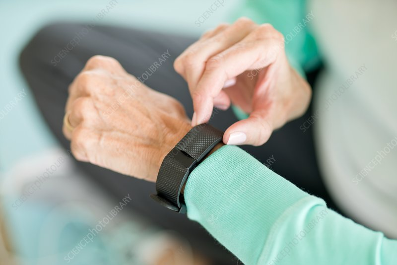 Senior woman using fitness tracker on wrist