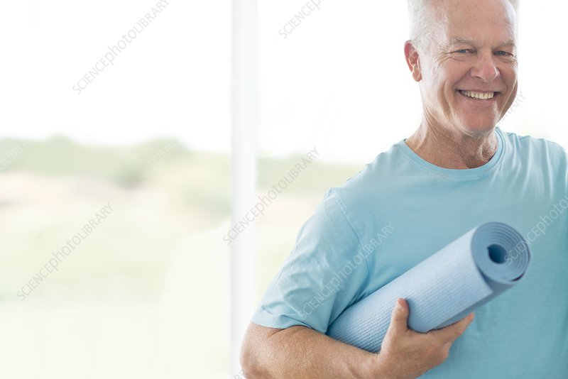 Senior man holding yoga mat