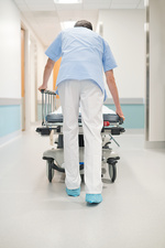 Nurse orderly pushing bed down corridor