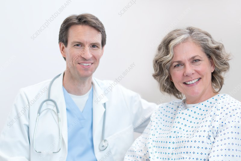 Doctor and female patient smiling towards camera