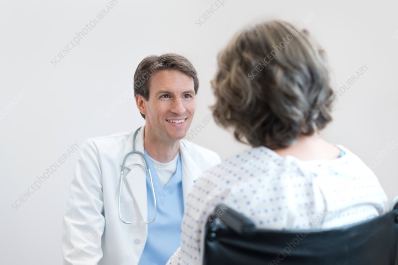 Doctor smiling at Woman patient in wheelchair