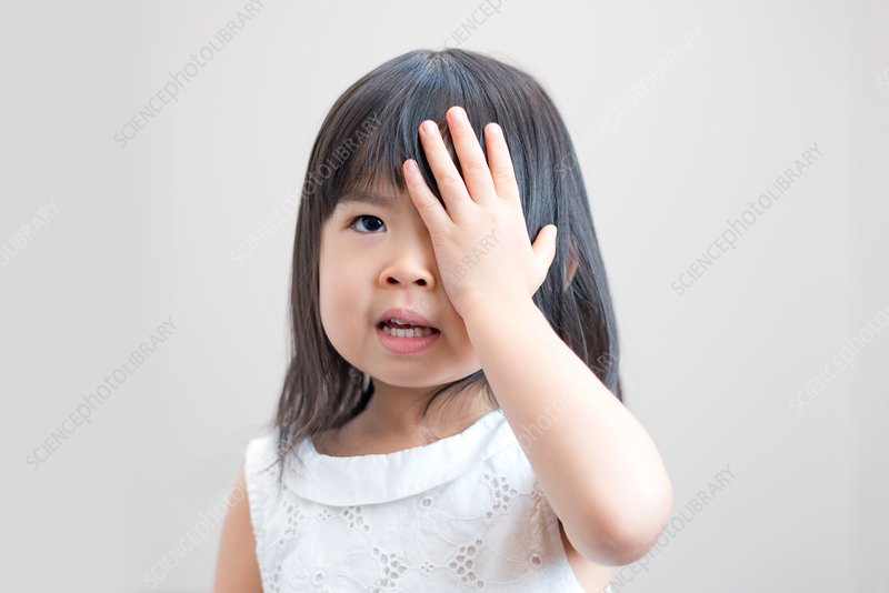 Young girl covering eye with hand