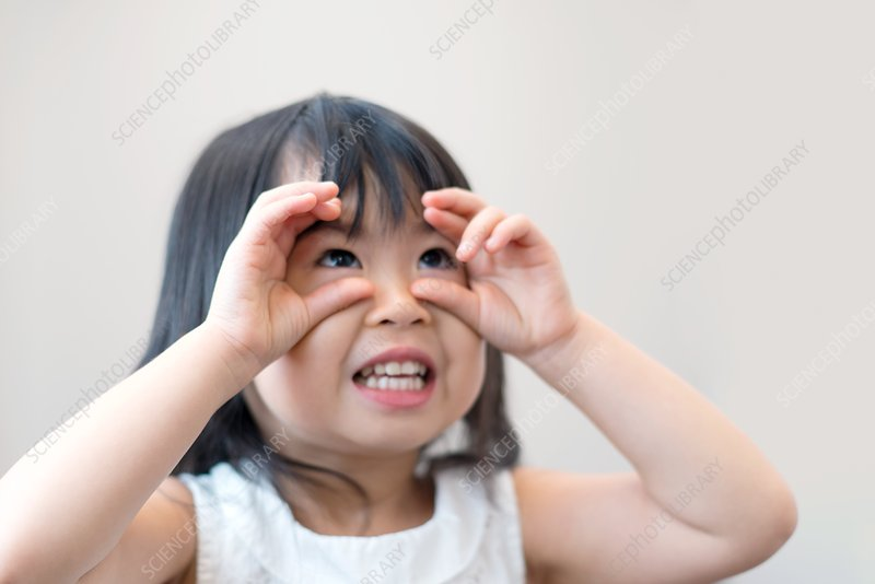Young girl with finger round eyes