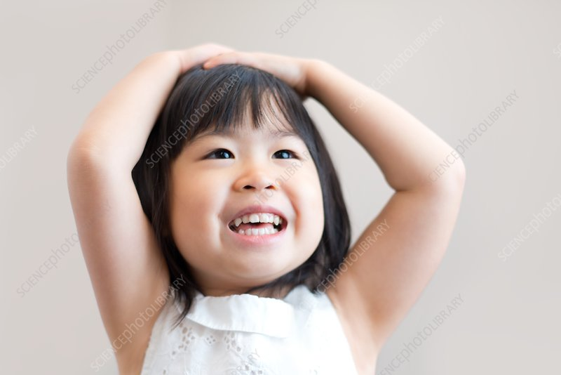 Young girl with hands on head smiling
