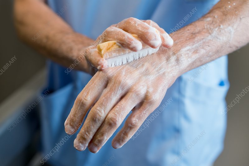 Doctor scrubbing hands with brush