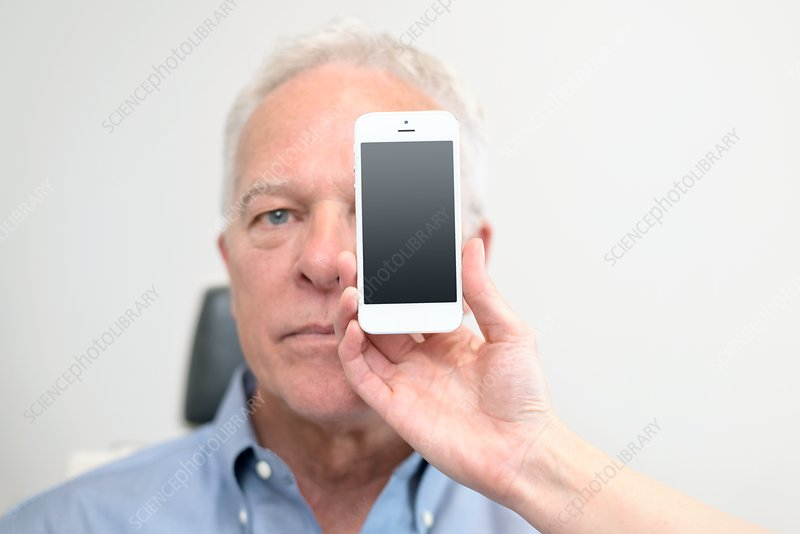 Man with smartphone covering eye
