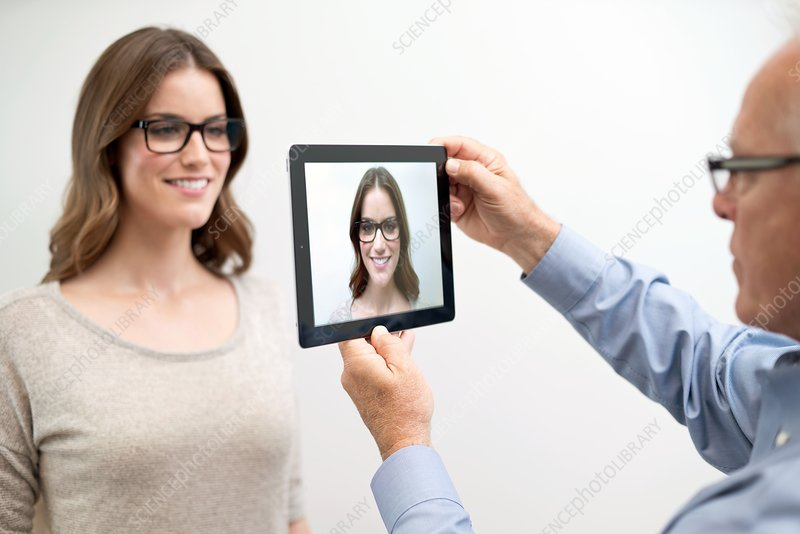Man holding digital tablet in front of woman's face