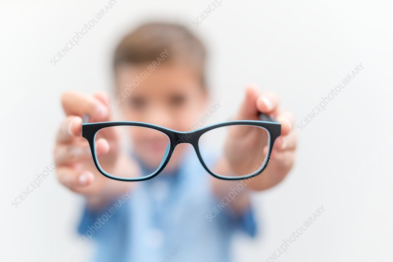 Boy holding glasses close up