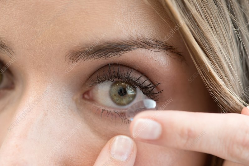 Mid adult woman putting contact lens in eye