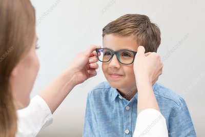Female optician putting glasses on boy