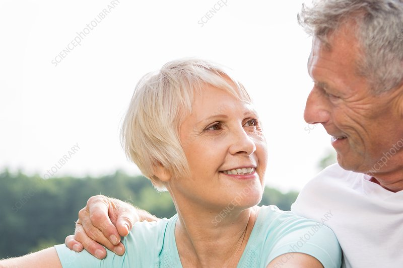 Senior couple smiling, man with arm around woman