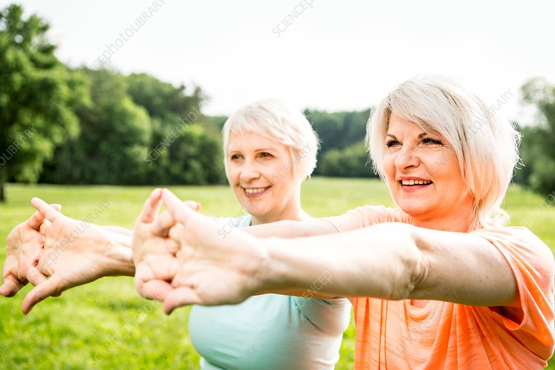 Two women exercising with arms outstretched