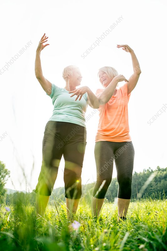 Two women exercising with arms raised
