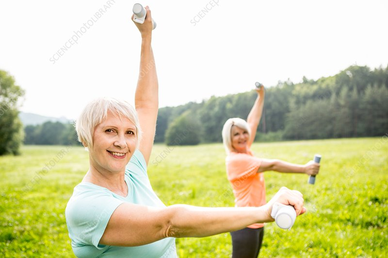 Two women exercising with hand weights