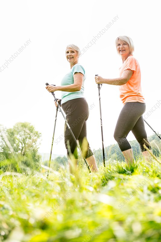 Two women walking in grass with walking poles