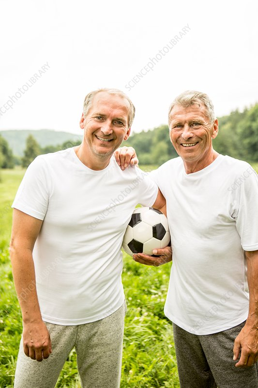 Two men with arms around each other holding football