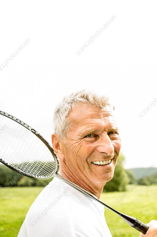 Man holding badminton rackets, smiling
