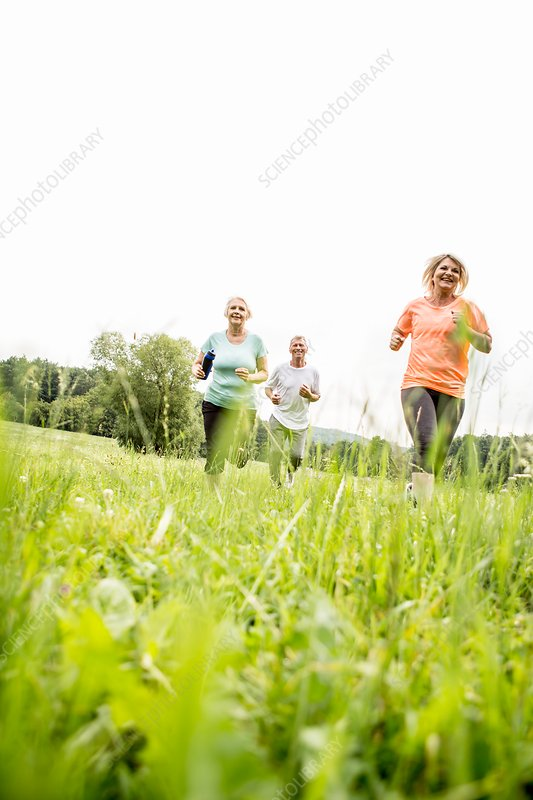 Three people running in field