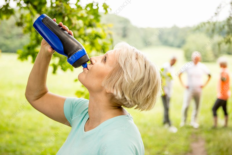 Senior woman drinking water from sports bottle
