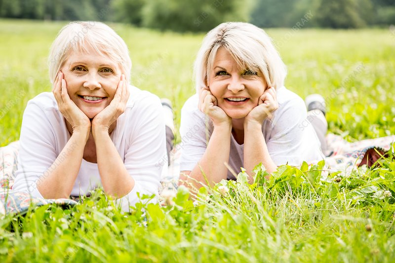 Two women lying on grass with hands on chin