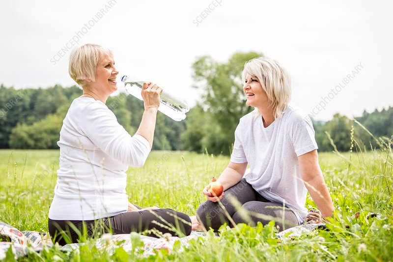 Two women sitting on grass, one drinking water