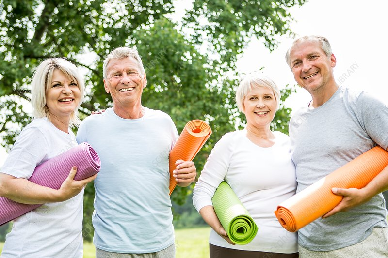 Four people with yoga mats, smiling