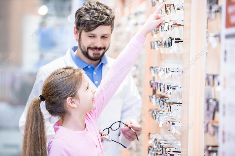 Young girl choosing glasses with optometrist