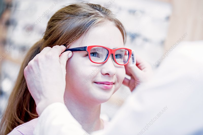 Optometrist trying glasses on girl