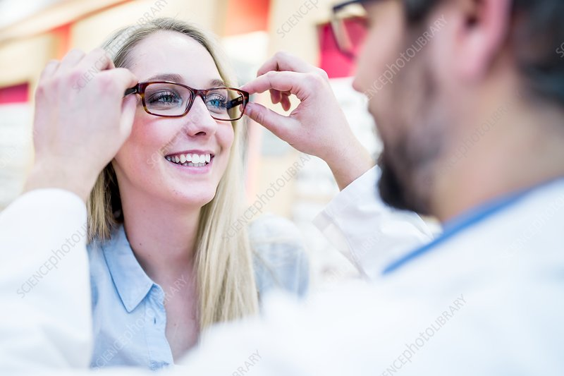 Optometrist trying glasses on woman
