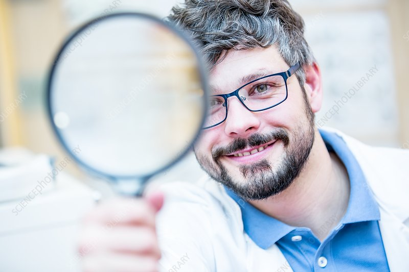 Optometrist holding magnifying glass