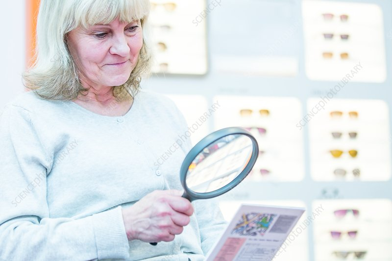 Senior woman holding magnifying glass