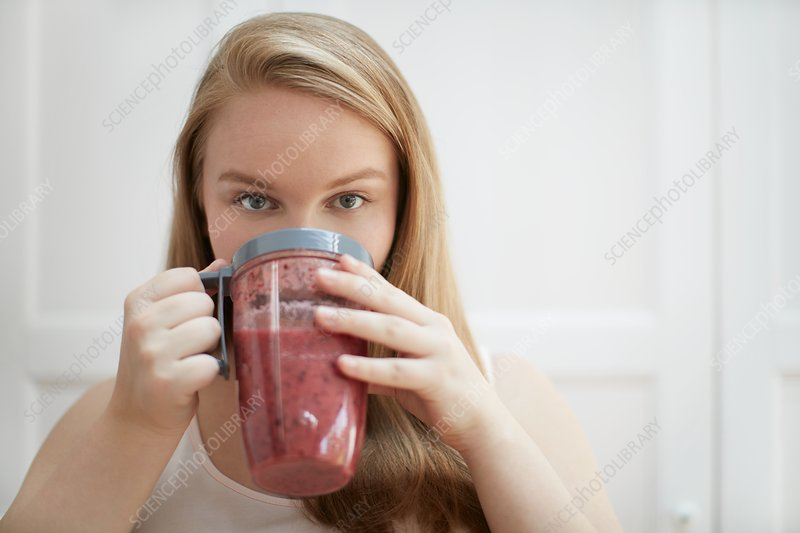 Young woman drinking homemade smoothie