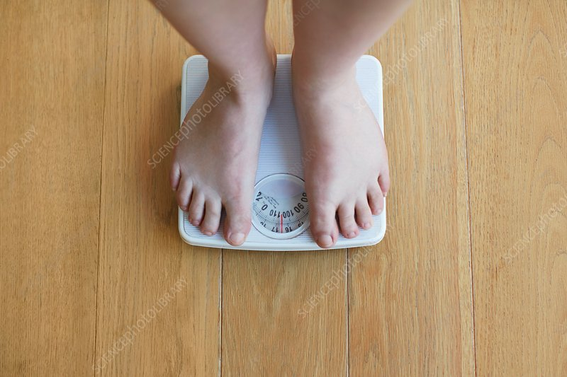 Young Woman Standing On A Scale Stock Image - Image of