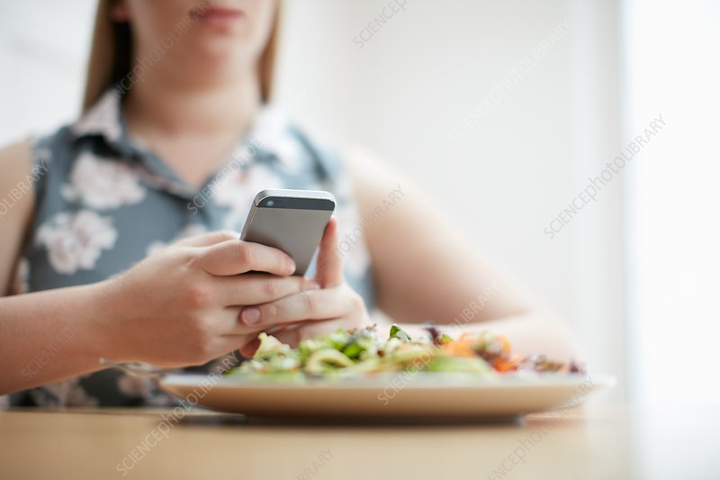 Woman using smartphone with plate of food in foreground