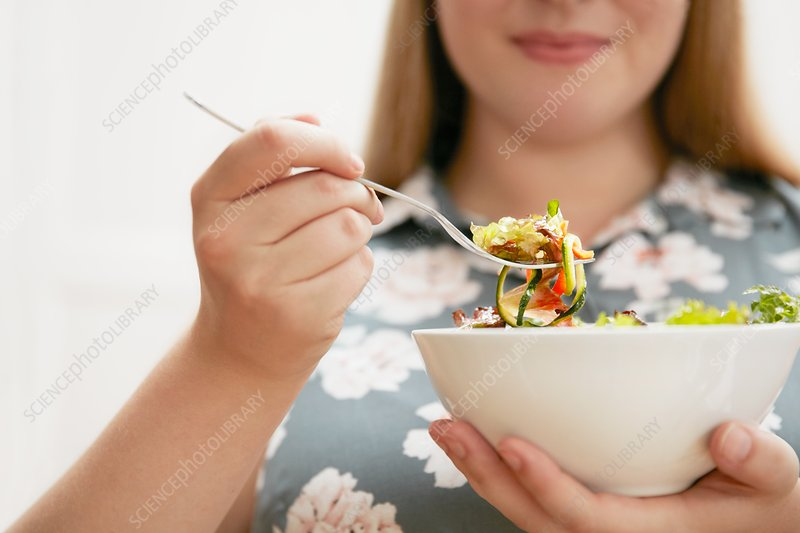 Young woman eating bowl of salad
