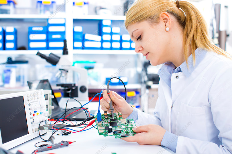 Female engineer soldering a circuit board