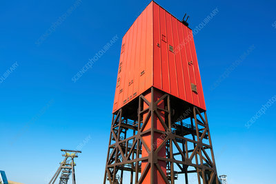 Red drilling rig against a clear blue sky