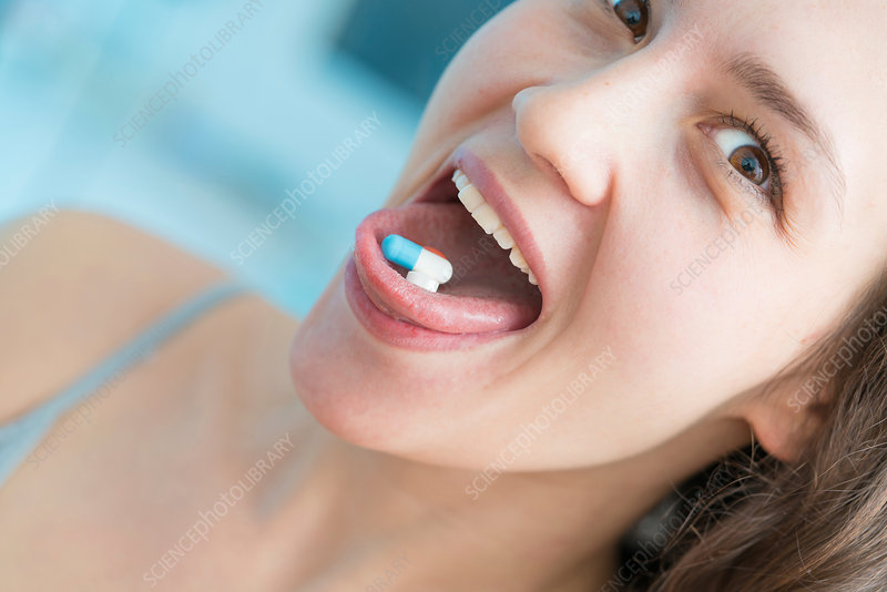 Woman with pills on tongue