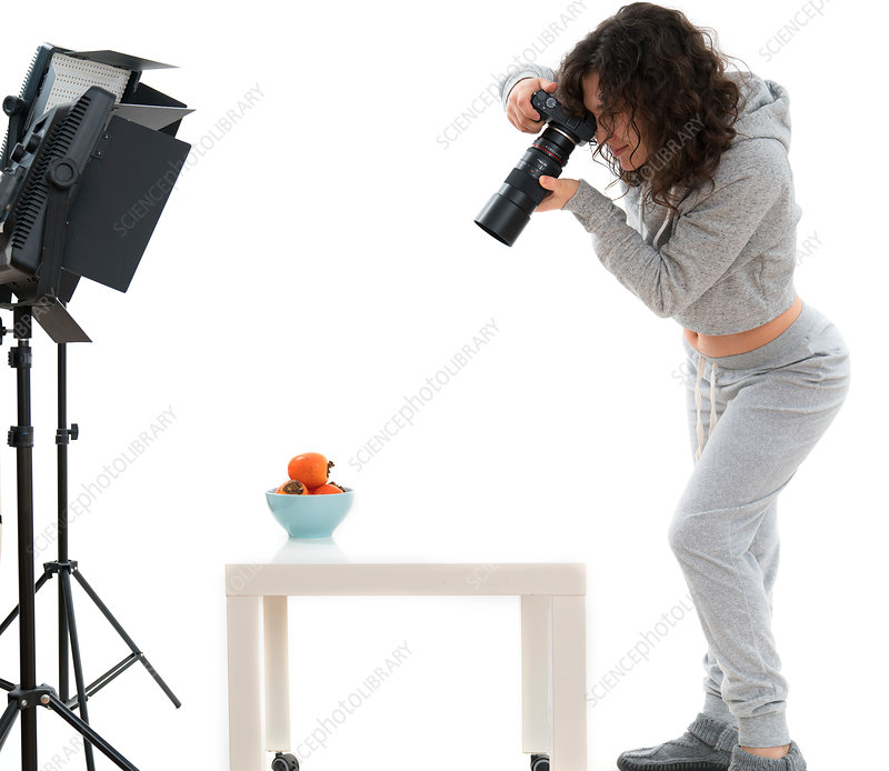 Female photographer in studio shooting still life