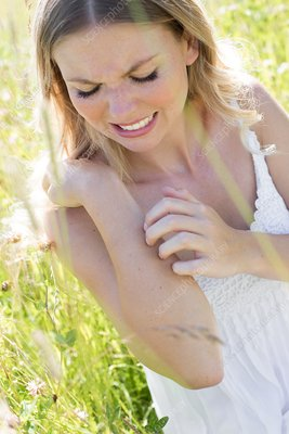 Woman in meadow scratching arm