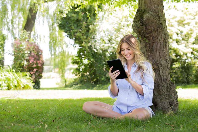Woman sitting by tree suing digital tablet