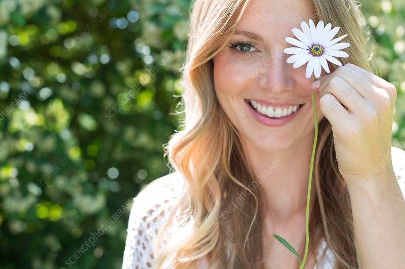 Woman holding daisy in front of eye