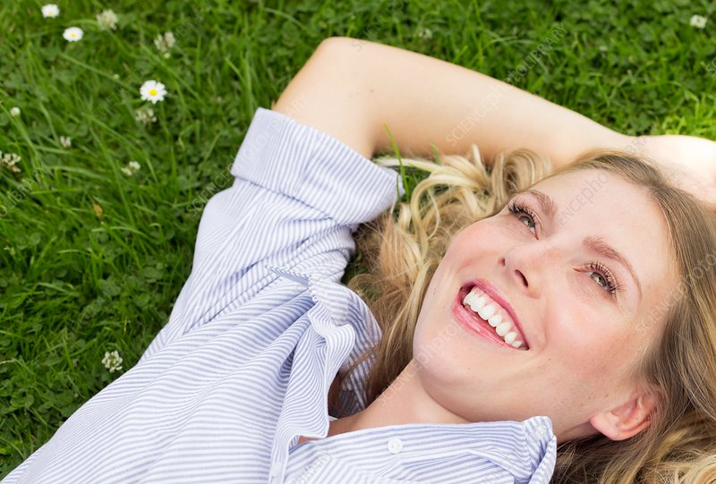 Woman lying on grass smiling