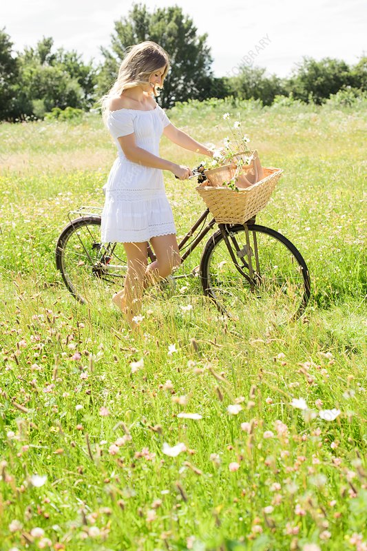 Woman in meadow with bicycle