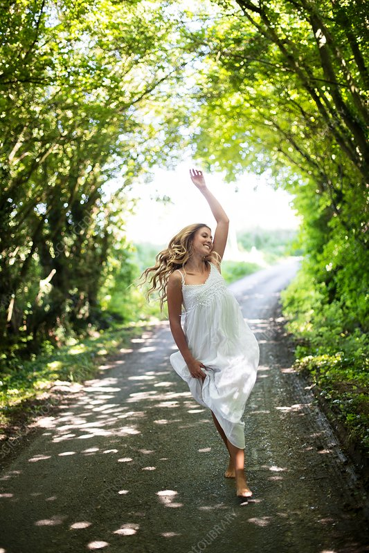 Young woman dancing on country lane