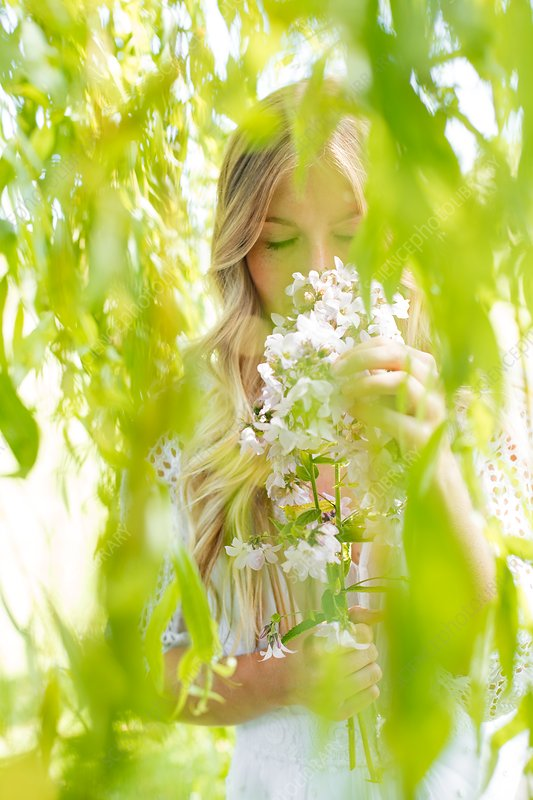 Woman smelling white flowers