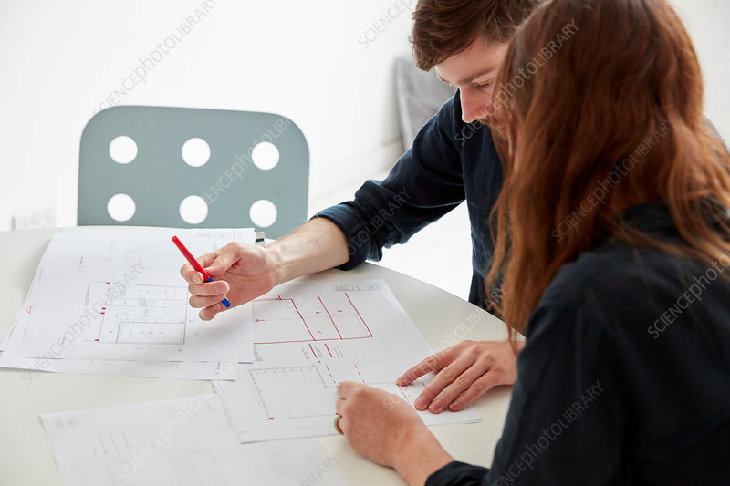 Two people, architects at a meeting with plans and drawings