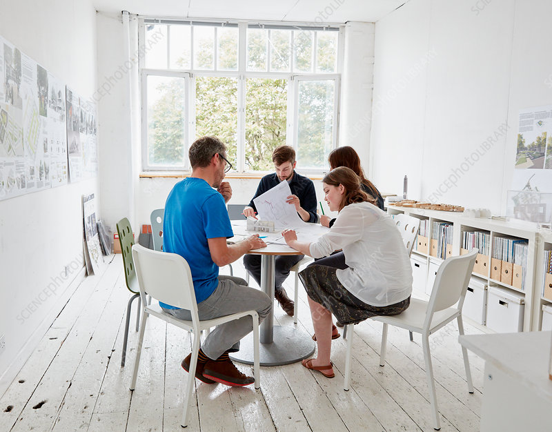 Two men and two women at a table with plans and papers